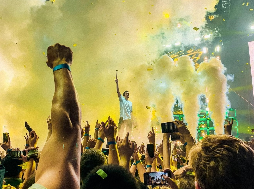 Tyler Joseph of Twenty One Pilots on stage in a cloud of smoke and confetti